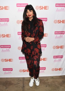 jameela jamil in a black suit with red floral pattern
