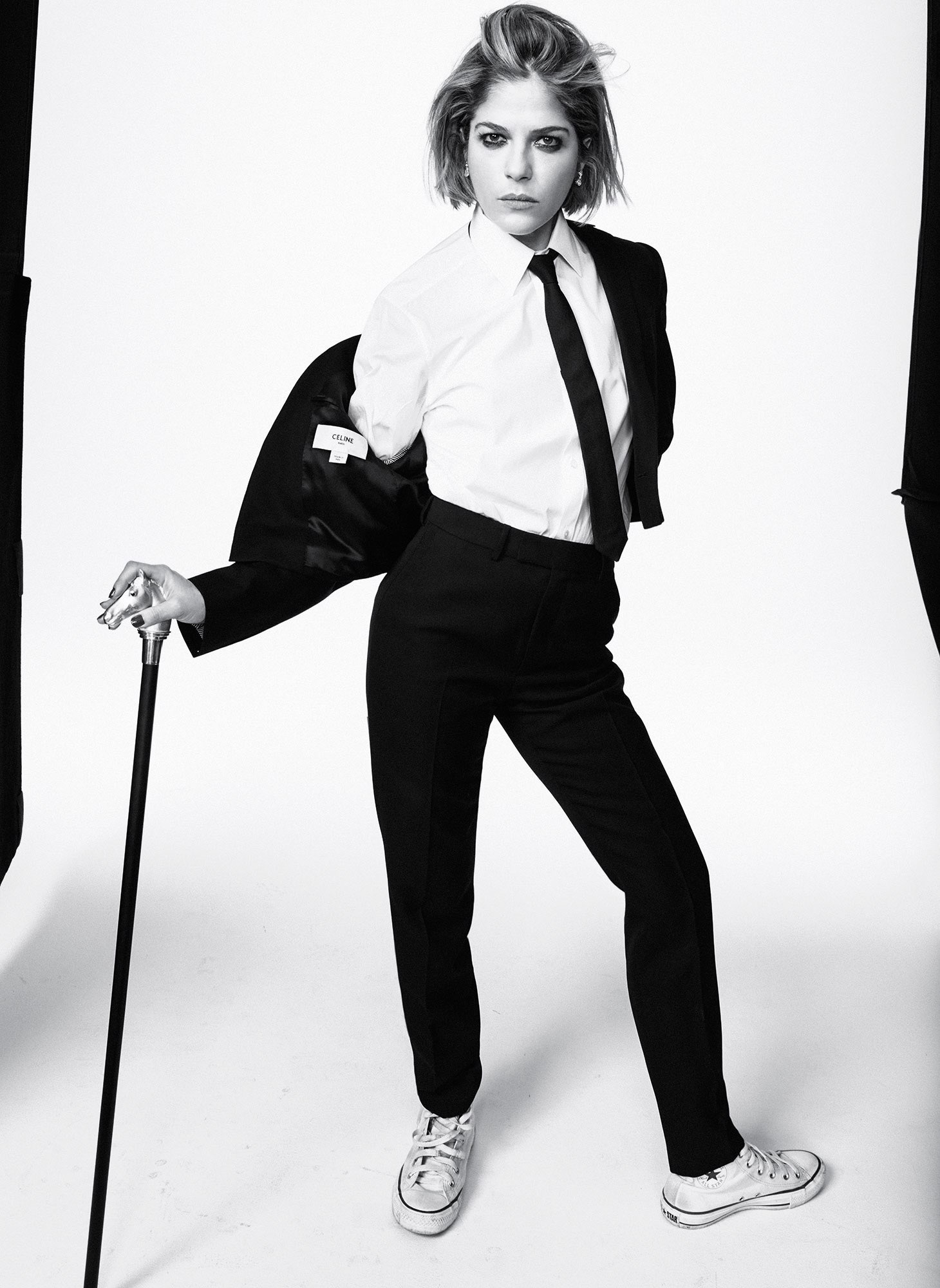 selma blair in a black suit using a cane